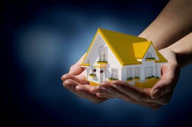 Human hands holding model of dream house.jpeg